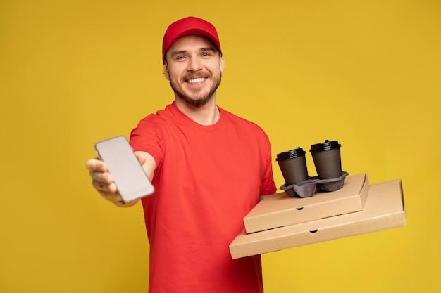 黄色の壁に分離されたピザとスマートフォンを保持している