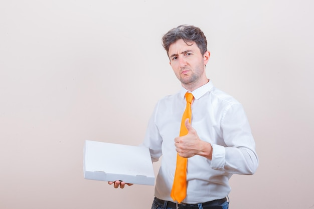 피자 상자를 들고, 셔츠, 청바지 전면보기에 엄지 손가락을 보여주는 젊은 남자.