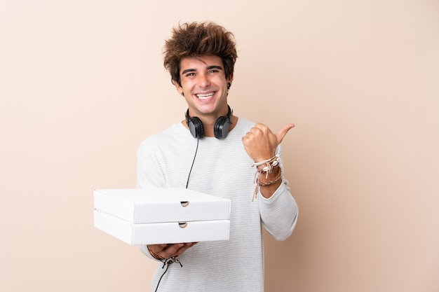 Young man holding pizza boxes over isolated wall