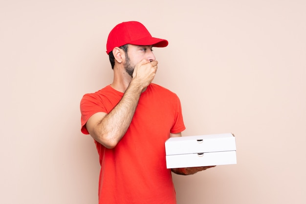Young man holding a pizza covering mouth and looking to the side
