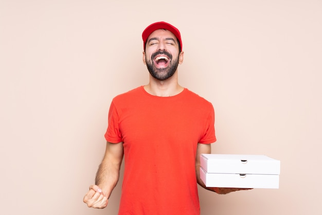 Young man holding a pizza over isolated background shouting to the front with mouth wide open