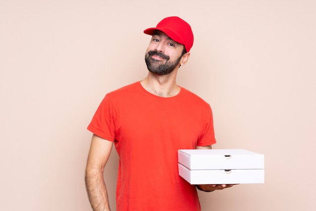 Young man holding a pizza over isolated wall laughing