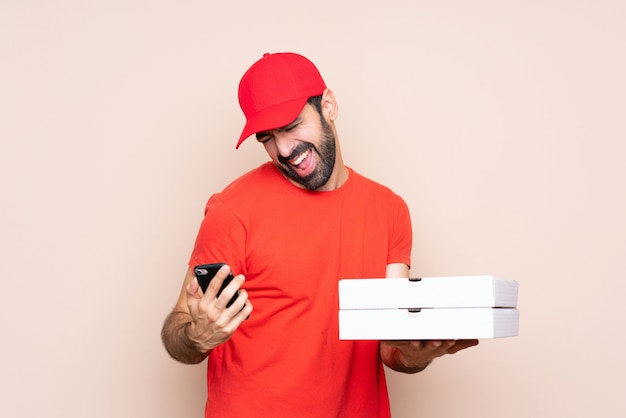 Young man holding a pizza over isolated wall with phone in victory position