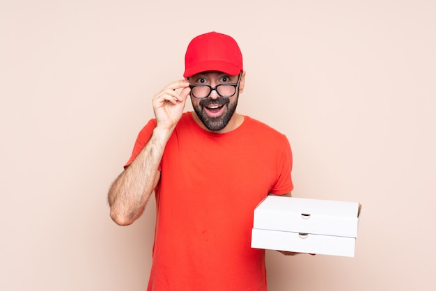 Young man holding a pizza over isolated  with glasses and surprised