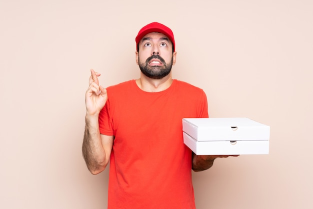 Young man holding a pizza with fingers crossing and wishing the best