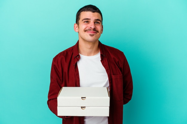 Young man holding pizzas isolated on blue wall dreaming of achieving goals and purposes