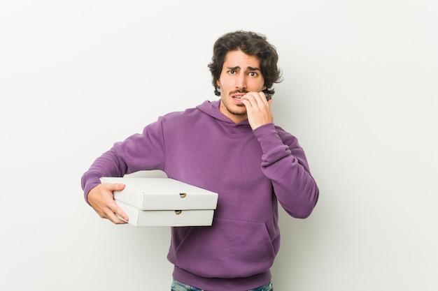 Молодой человек, держащий пакет пиццы, кусающий ногти, нервный и очень взволнованный.