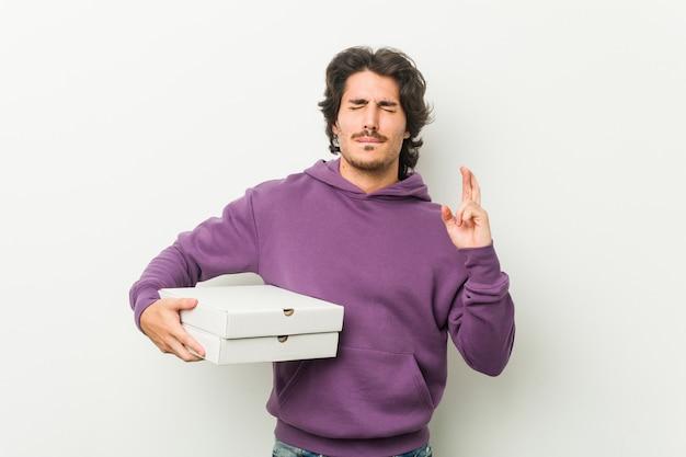 Молодой человек, держащий пакет пиццы, скрестив пальцы за удачу