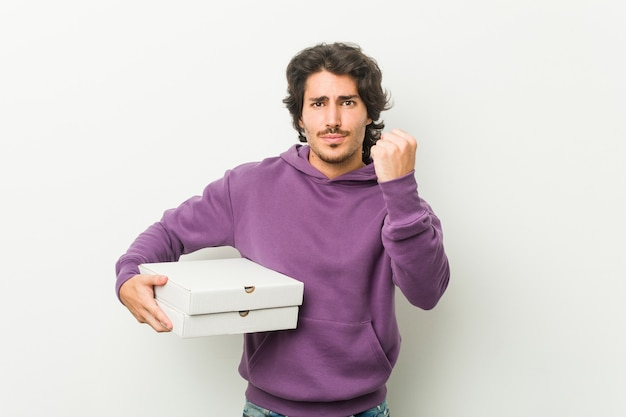 Young man holding pizzas package showing fist to camera, aggressive facial expression.