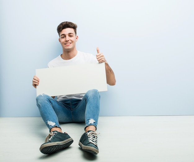 Young man holding a placard sitting on his home floor smiling and raising thumb up