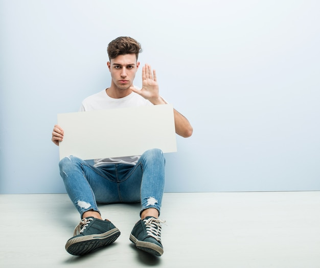 Young man holding a placard sitting on his home floor standing with outstretched hand showing stop sign, preventing you.
