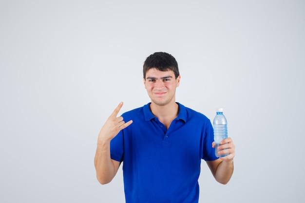 Молодой человек держит пластиковую бутылку, демонстрирует рок-жест в футболке и выглядит уверенно. передний план.