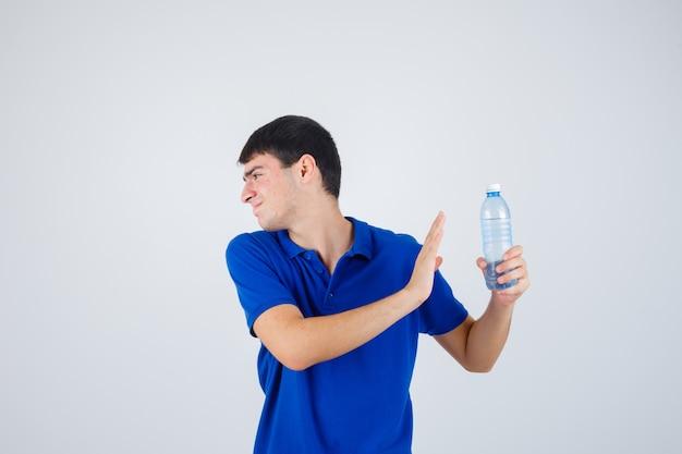 Молодой человек держит пластиковую бутылку, показывает жест в футболке и выглядит раздраженным. передний план.
