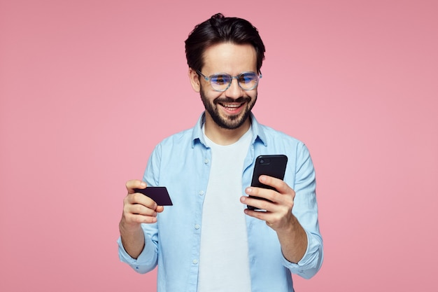 분홍색 벽에 플라스틱 신용 카드와 휴대 전화를 들고 젊은 남자