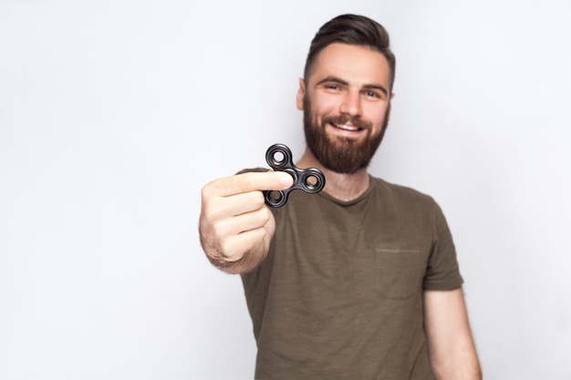 Young man holding and playing with fidget spinner. looking at camera. studio shot on white background. .