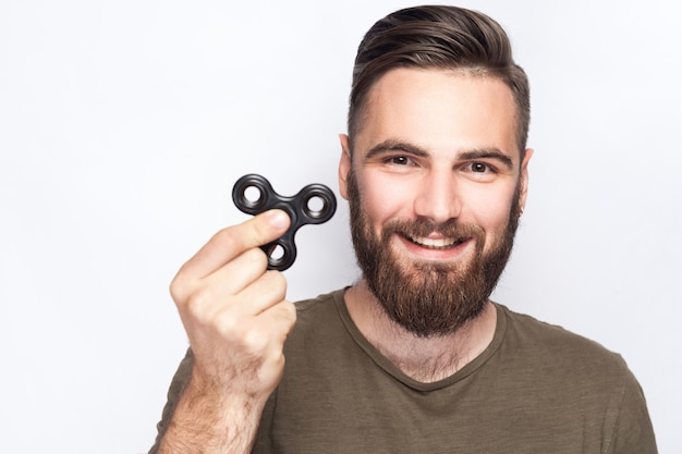 Young man holding and playing with fidget spinner. studio shot on white background. .