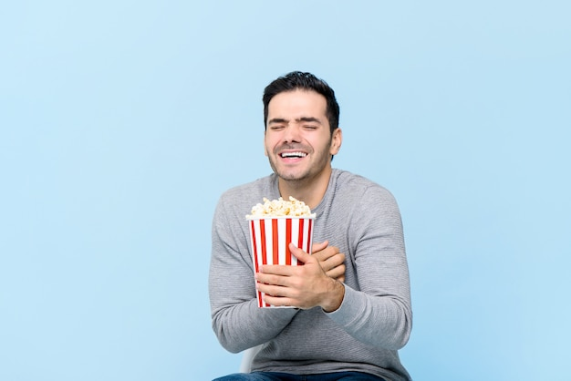 Young man holding popcorn laughing while watching movie isolated on light blue wall