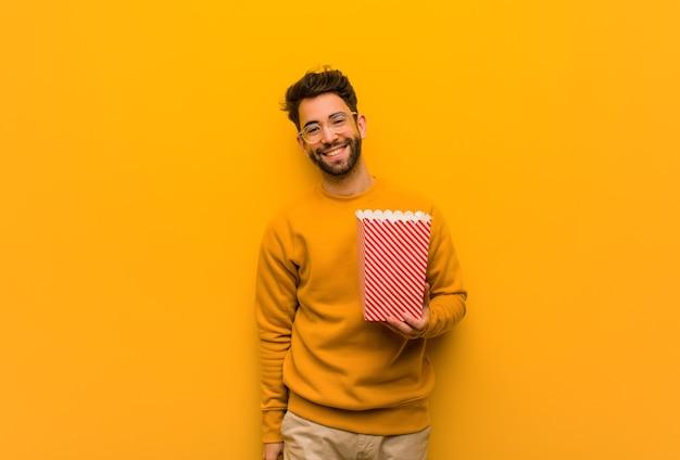 Молодой человек, держащий попкорн, скрещивает руки, улыбается и расслабляется