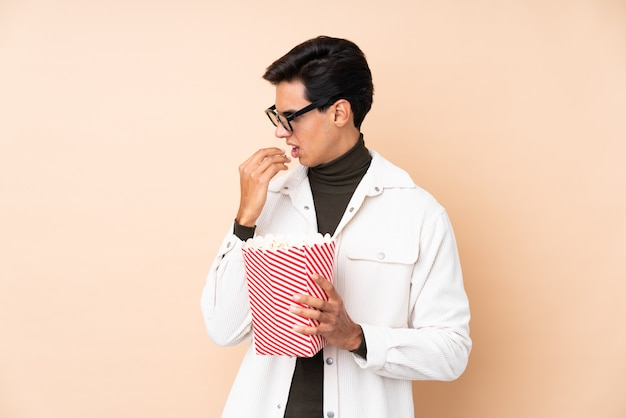 Young man holding popcorns over isolated wall