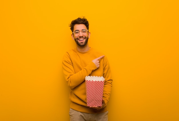 Young man holding popcorns pointing to the side with finger