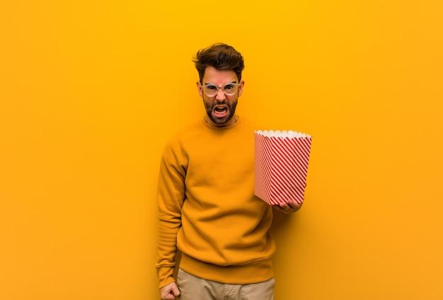 Молодой человек держит попкорн кричать очень злой и агрессивный