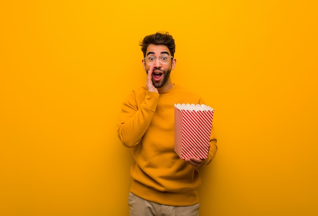 Young man holding popcorns shouting something happy to the front