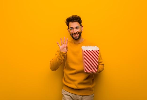 Молодой человек держит попкорн, показывая номер четыре