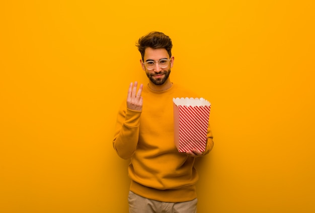 Young man holding popcorns showing number three