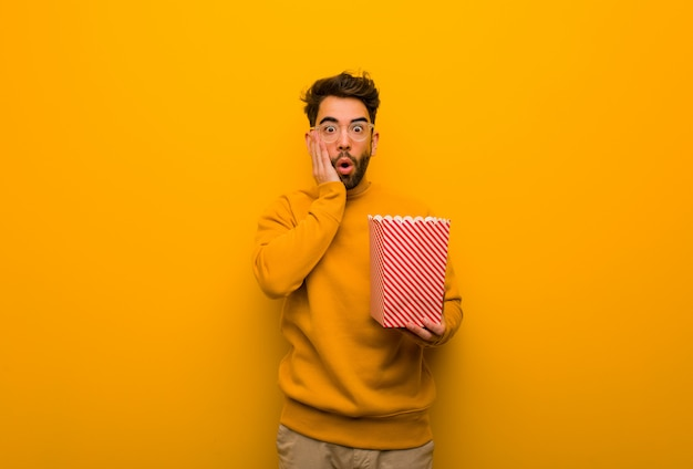 Young man holding popcorns surprised and shocked
