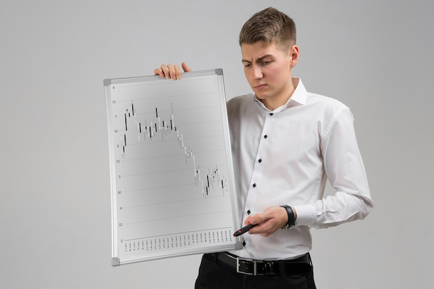 Young man holding a poster with statistics isolated on a light background