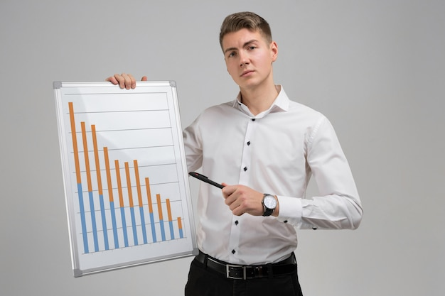 Young man holding a poster with statistics isolated on light