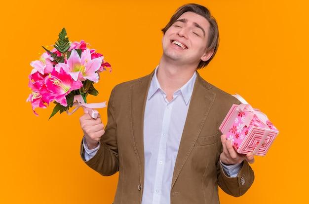 현재와 꽃의 꽃다발을 들고 젊은 남자가 행복하고 흥분된 미소가 오렌지 벽 위에 서있는 국제 여성의 날을 축하하려고합니다.