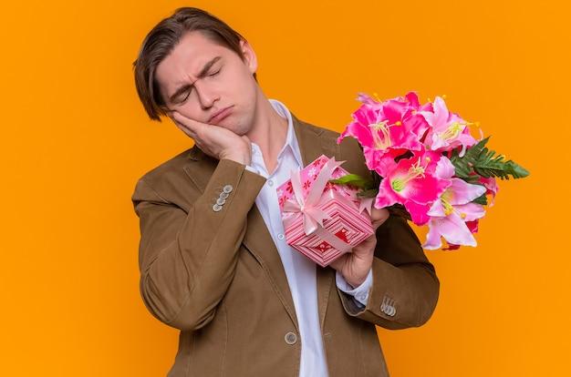 오렌지 벽 위에 서있는 국제 여성의 날을 축하하려고 피곤하고 지루해 보이는 현재와 꽃의 꽃다발을 들고 젊은 남자