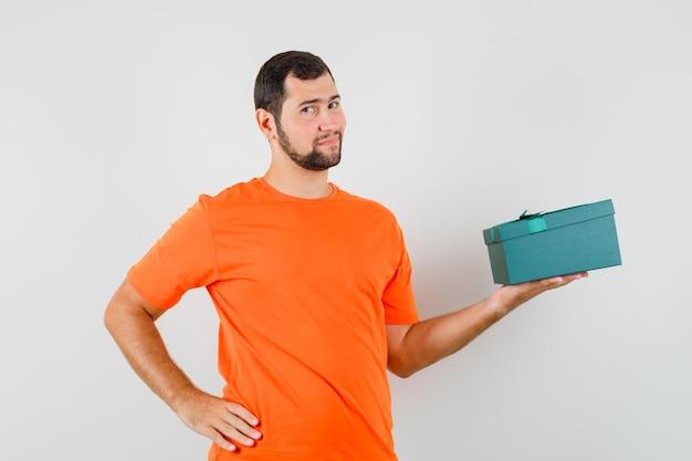 オレンジ色のtシャツでプレゼントボックスを保持し、自信を持って、正面図を探している若い男。