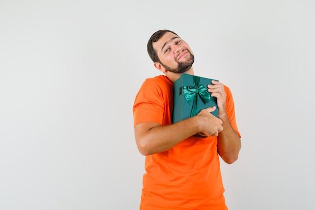 オレンジ色のtシャツでプレゼントボックスを持って、かわいく見える若い男。正面図。