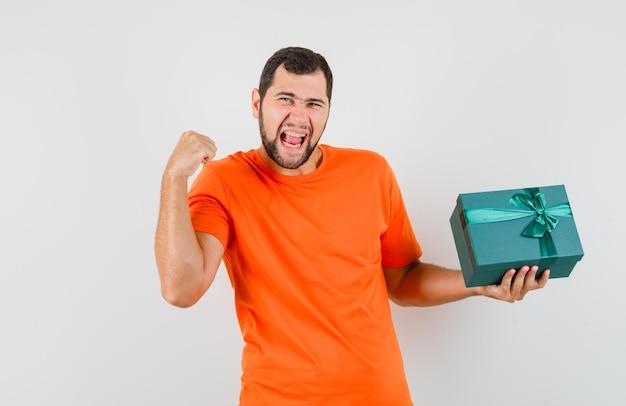 オレンジ色のtシャツで成功ジェスチャーでプレゼントボックスを保持し、幸運に見える若い男。正面図。