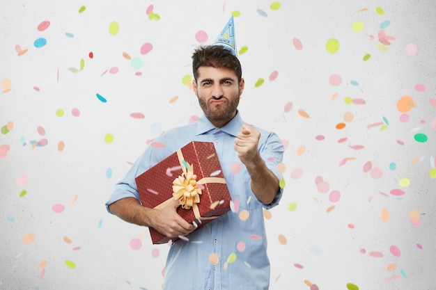 Young man holding present surrounded by confetti
