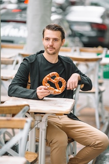 Young man holding pretzel and relaxing in park