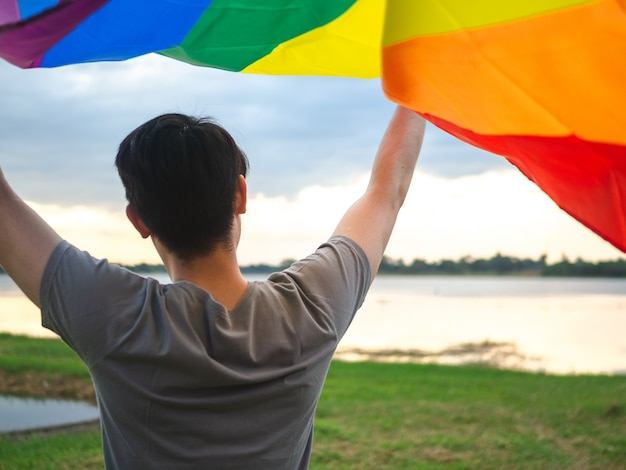 Young man holding a rainbow flag over his head beside the lake on sunset sky background.