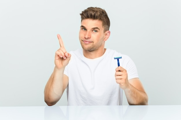 Young man holding a razor blade showing number one with finger.
