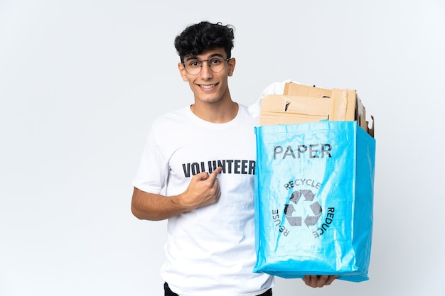 Young man holding a recycling bag full of paper with surprise facial expression