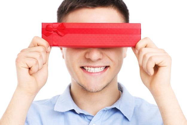 흰색 배경 위에 빨간색 선물을 들고 젊은 남자