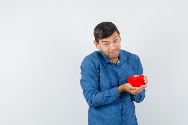 青いシャツに赤いハートを持って陽気に見える若い男。正面図。