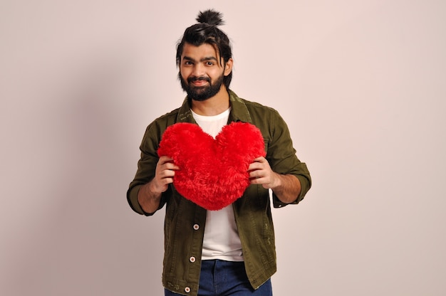 Young man holding a red heart shaped pillow for valentines day