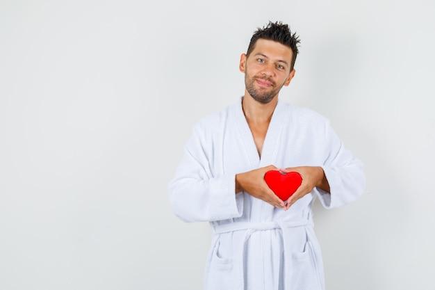 Giovane che tiene cuore rosso in accappatoio bianco e che sembra gioioso. vista frontale.