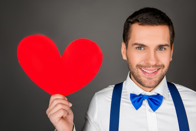 Young man holding red paper heart