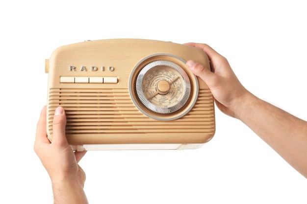 白いスペースでレトロなラジオを保持している若い男