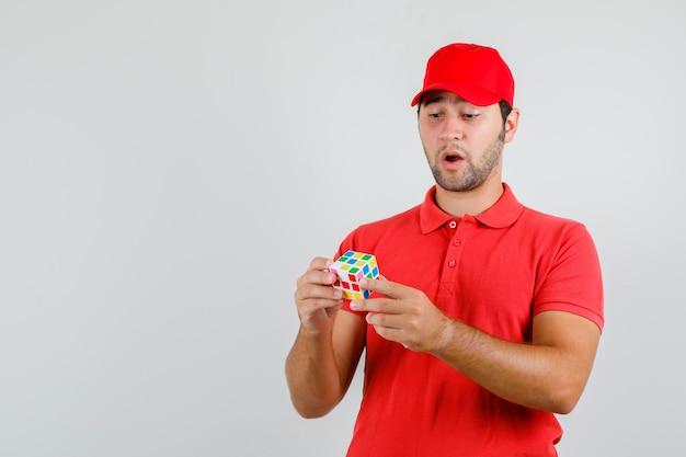 Молодой человек держит кубик рубика в красной футболке, кепке и выглядит смущенным.