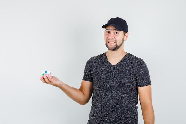 Молодой человек держит кубик рубика в футболке и кепке и выглядит весело