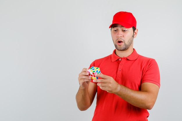 Young man holding rubik's cube in red t-shirt, cap and looking confused.